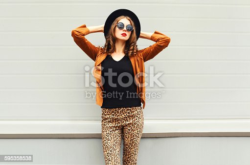 istock Fashion woman model wearing black hat, sunglasses, jacket over background 595358538