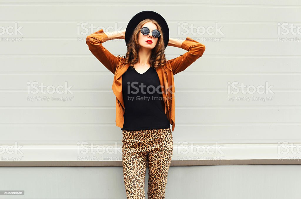 Fashion woman model wearing black hat, sunglasses, jacket over background stock photo