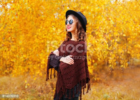 istock Fashion woman model wearing black hat sunglasses knitted poncho autumn 614026310