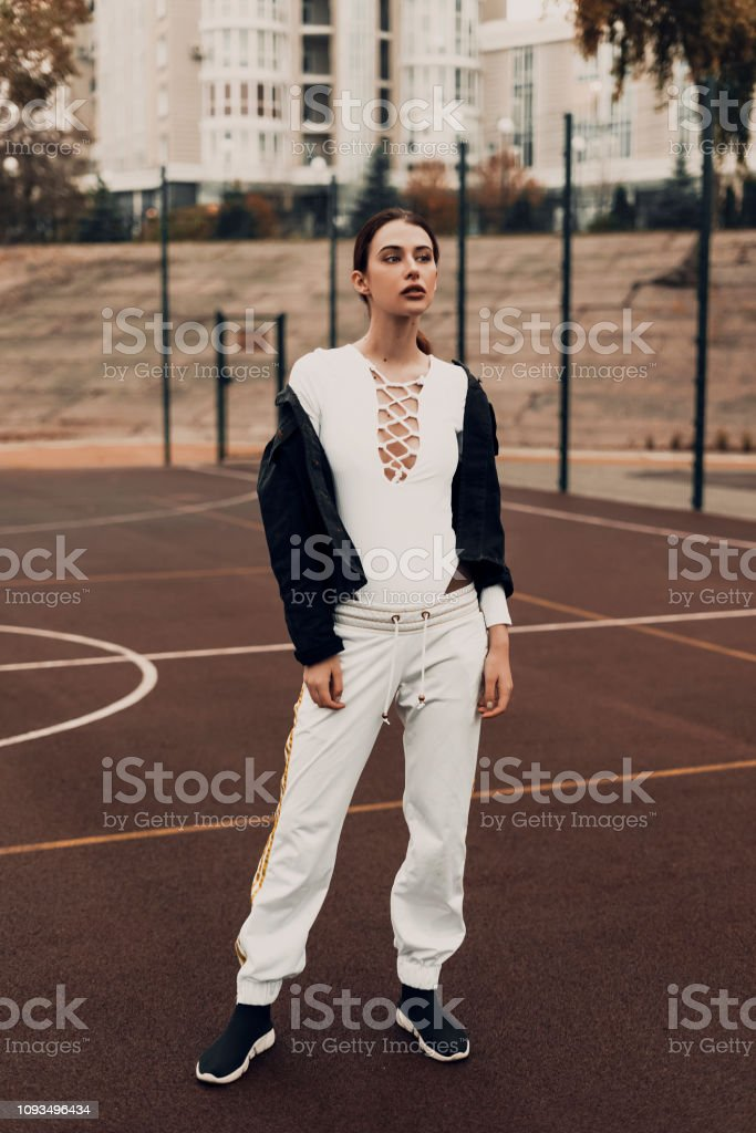 Fashion woman model young beauty posing on sports ground. Street...