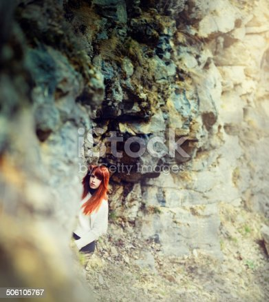 red hair attracitve woman posing outdoors in rocks landscape.