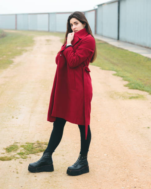 Fashion woman portrait of young pretty girl posing in a rural scene in Europe. Winter and spring fashion, wearing a red jacket. stock photo
