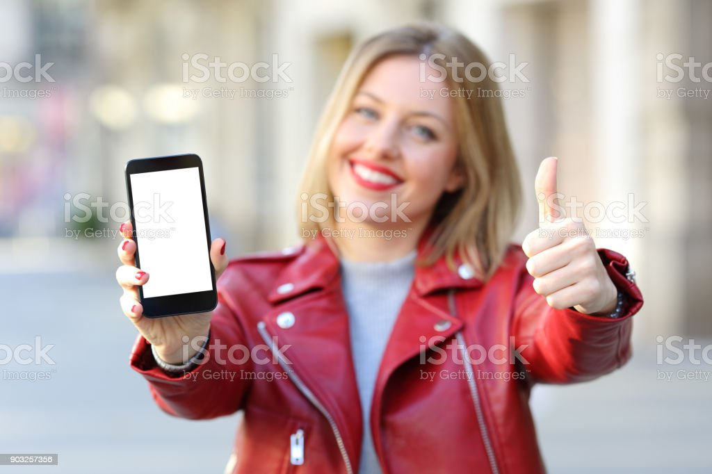 Fashion woman showing a smartphone screen on the street royalty-free stock photo