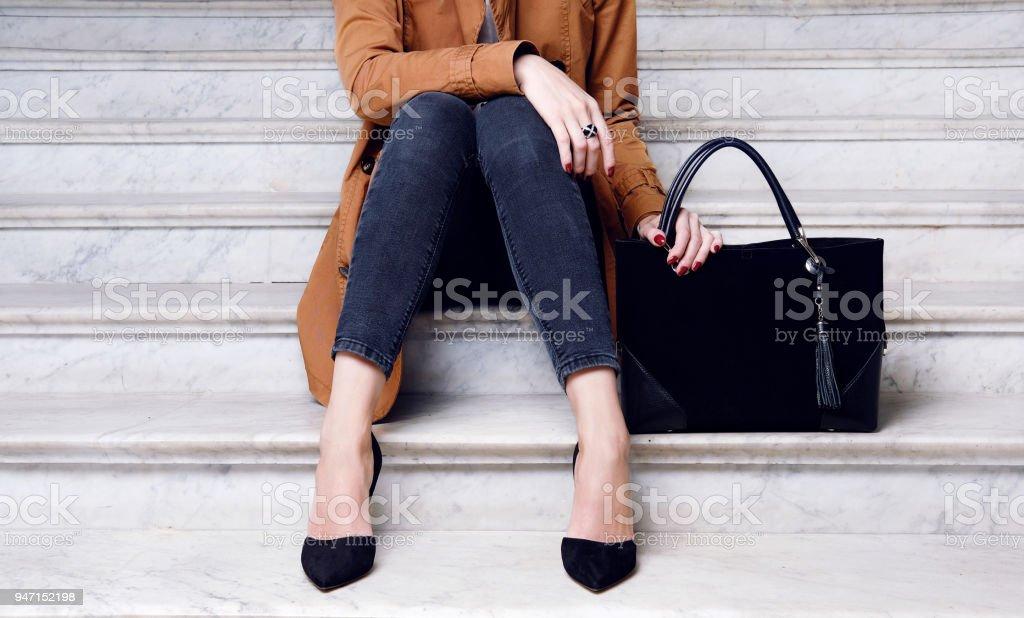Moda mulher sente-se em sapatos de salto alto segura saco grande preto - foto de acervo