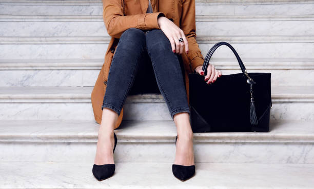 fashion woman sit in high heels shoes hold black big bag - borsetta foto e immagini stock