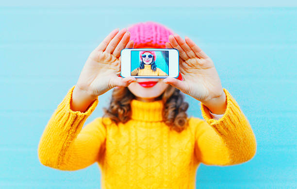 Fashion woman taking photo self portrait on smartphone over blue stock photo