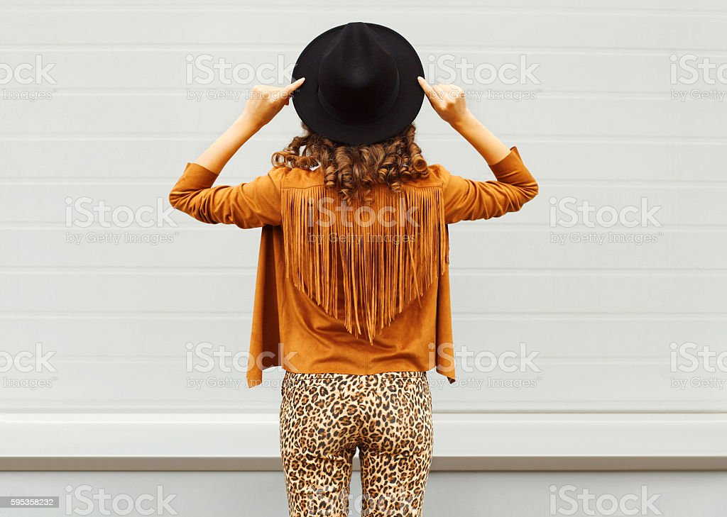 Fashion woman view from back wearing black hat, sunglasses jacket stock photo