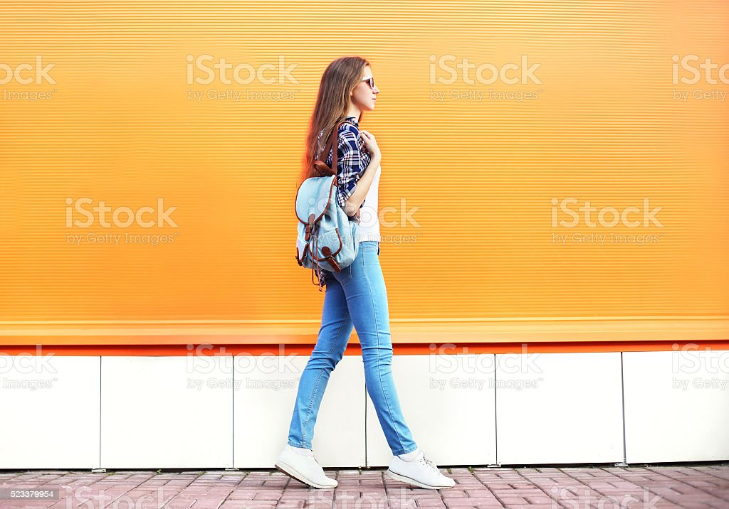 Fashion woman walking in city over colorful orange background stock photo
