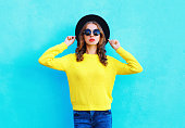 Fashion portrait pretty woman wearing a black hat and yellow knitted sweater over colorful blue background