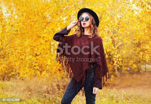 469211680 istock photo Fashion woman wearing a black hat sunglasses knitted poncho autumn 614026266