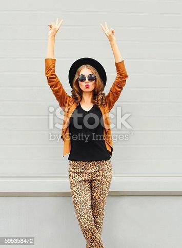 istock Fashion woman wearing black hat, sunglasses jacket raises hands up 595358472