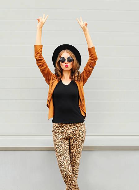 fashion woman wearing black hat, sunglasses jacket raises hands up - bedruckte leggings stock-fotos und bilder
