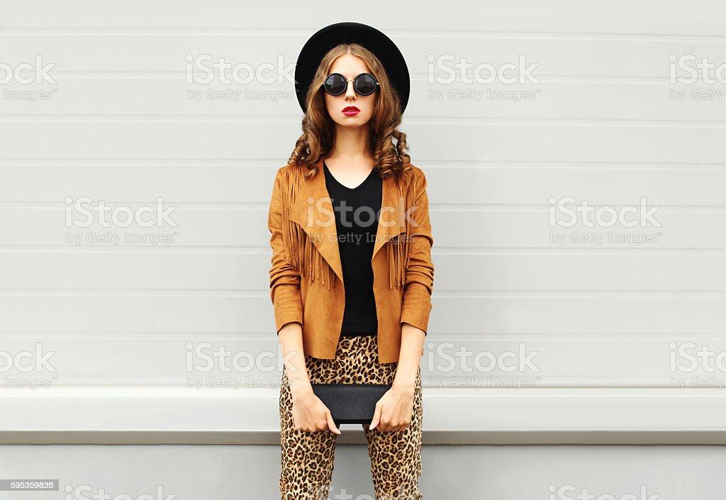 Fashion woman wearing elegant hat, jacket handbag clutch over background