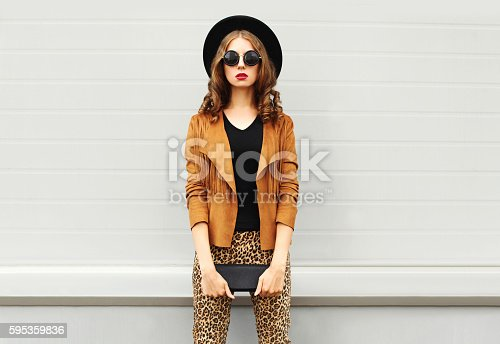 istock Fashion woman wearing elegant hat, jacket handbag clutch over background 595359836