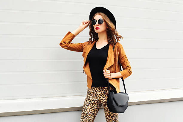 fashion woman wearing elegant hat, jacket walking in city - bedruckte leggings stock-fotos und bilder