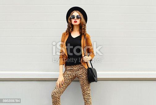 istock Fashion woman wearing hat, sunglasses, brown jacket and black handbag 595359784
