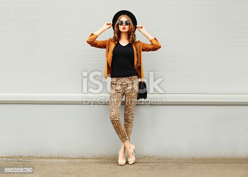 Fashion pretty young woman wearing a retro elegant hat, sunglasses, brown jacket and black handbag posing in city over grey background