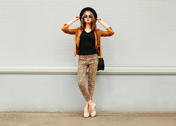 fashion woman wearing hat, sunglasses, jacket, handbag posing in city - mode automne photos et images de collection
