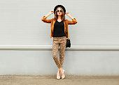 Fashion woman wearing hat, sunglasses, jacket, handbag posing in city