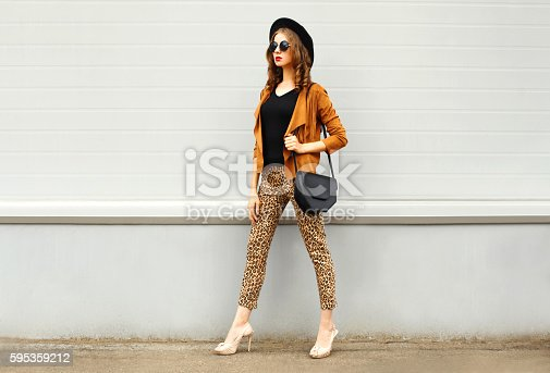 istock Fashion woman wearing hat, sunglasses, jacket, handbag walking in city 595359212