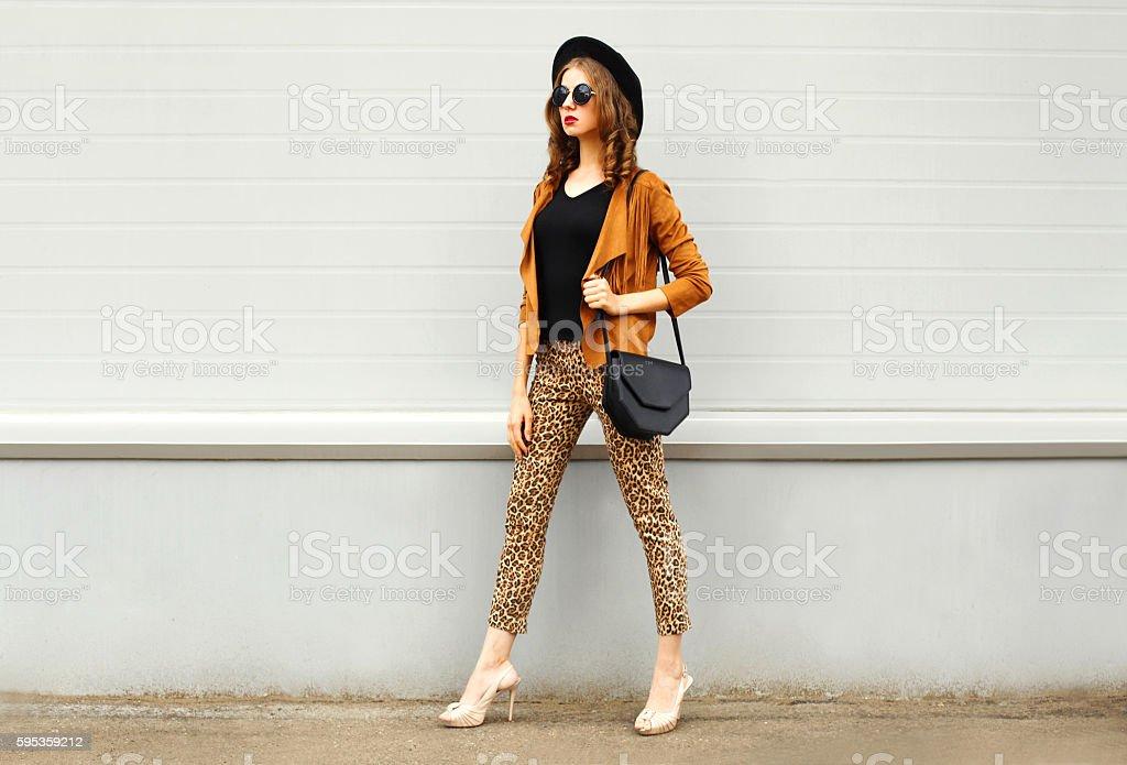 Fashion woman wearing hat, sunglasses, jacket, handbag walking in city stock photo