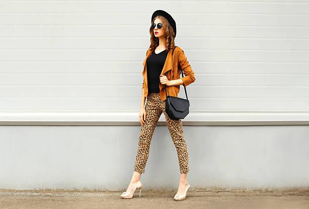 fashion woman wearing hat, sunglasses, jacket, handbag walking in city - bedruckte leggings stock-fotos und bilder