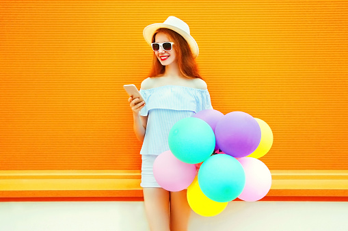 istock Fashion woman with an air colorful balloons is using the smartphone on a orange background 925284978