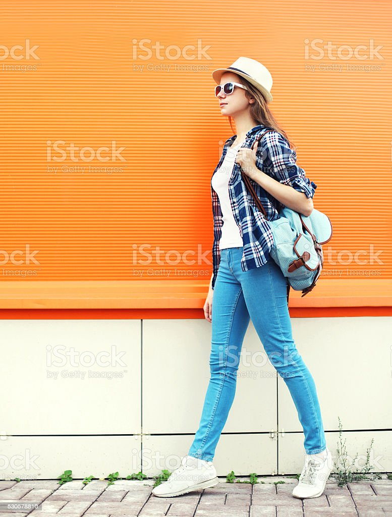 Fashion woman with backpack over colorful orange background stock photo