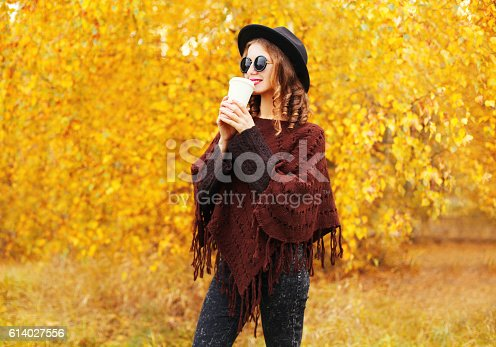 469211680 istock photo Fashion woman with coffee cup wearing black hat autumn poncho 614027556