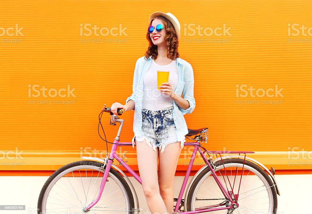 Fashion woman with coffee or juice cup and retro bicycle stock photo