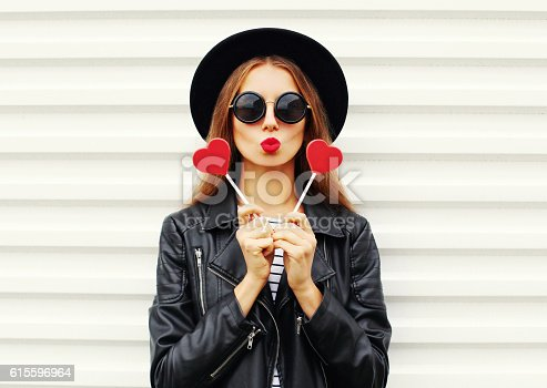 529664088istockphoto Fashion woman with red lips air kiss with lollipop heart 615596964