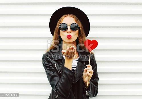529664088istockphoto Fashion woman with red lips sends air kiss lollipop heart 615596930