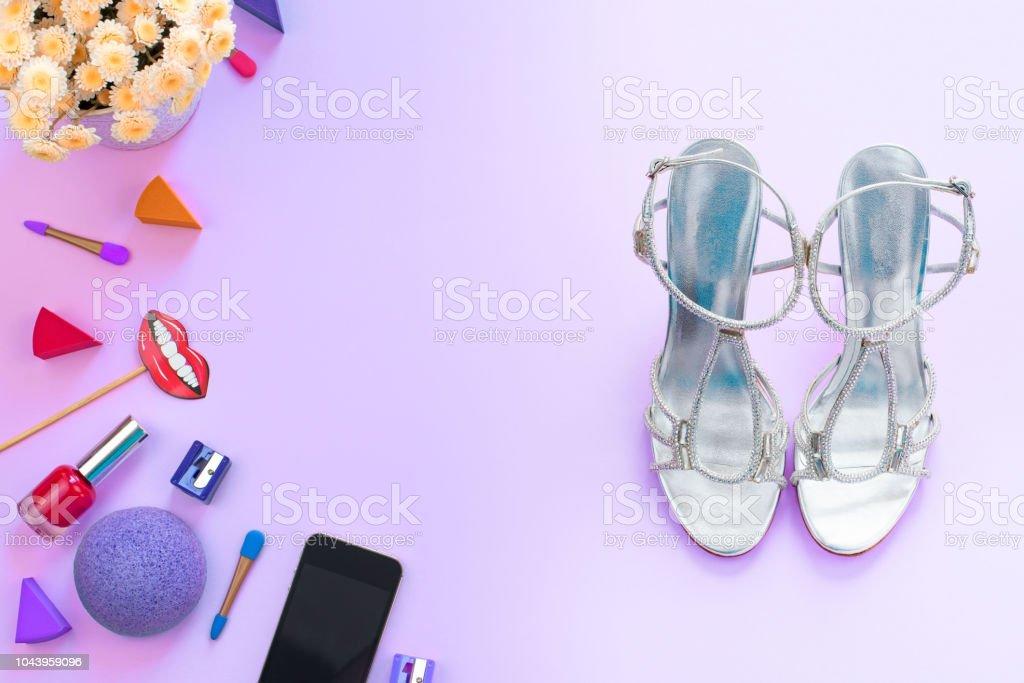 1be640063 Moda mujer accesorios cosméticos zapatos gadget móvil flores sobre fondo  púrpura superior ve espacio de copia. Abrir imagen para boceto