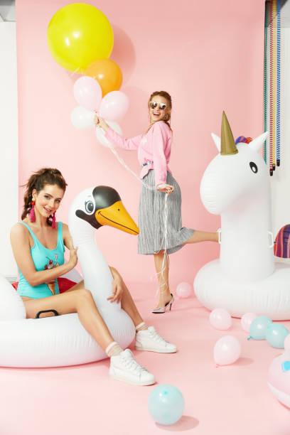 mode. frauen in bunten kleidern, die spaß am pool schwimmt - eis ballons stock-fotos und bilder