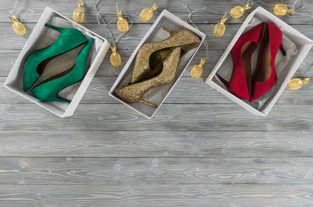 mode-damen-schuhe (pumpen) im schuhkarton. klassische weihnachtsfarben (rot, grün, gold). weihnachten urlaub konzept, lichterketten. schuhe, hölzernen hintergrund kopieren raum. vorlage für online-shop, website, banner. flach legen, top-down-ansicht - glitzer absätze stock-fotos und bilder