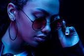 Fashion young African girl black woman hold stylish pink glasses looking at the camera isolated on a black Studio background, horizontal banner for website design, portrait, copy space