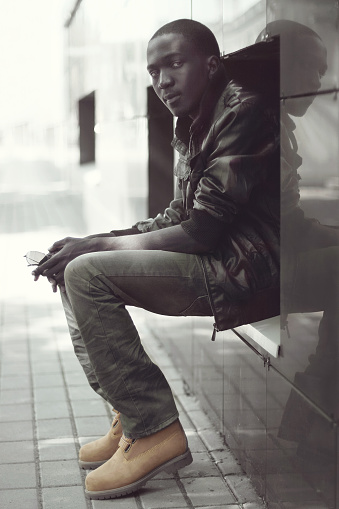 627398448 istock photo Fashion young african man sitting in the city, view profile 625299328