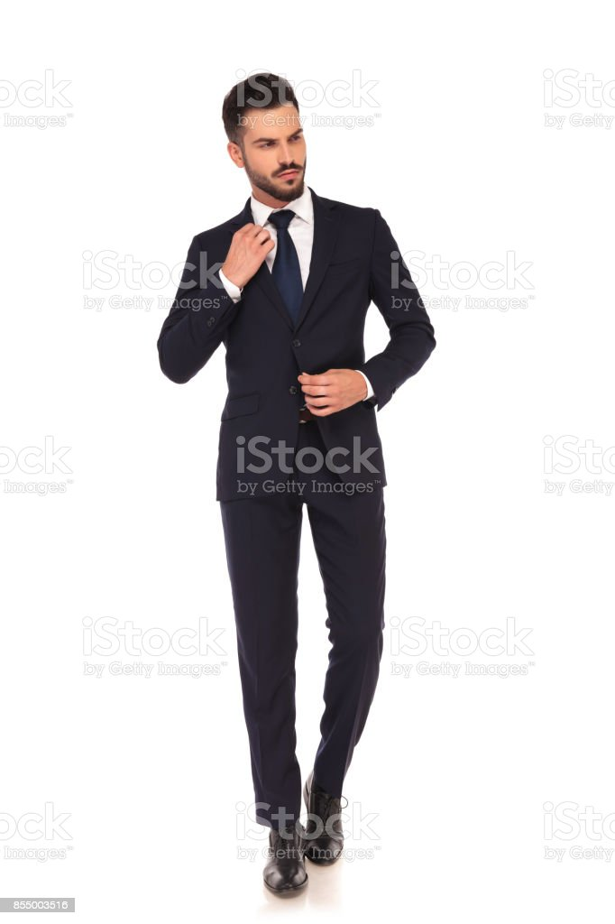 fashion young business man fixing his coat and collar stock photo