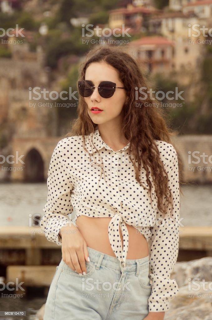 Jovem de moda com a saia de ploka-ponto andando na cidade velha, perto da água - Foto de stock de Adulto royalty-free