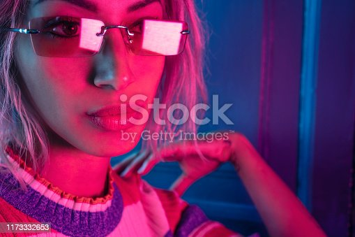 Fashion young girl portrait with neon red light and sunglasses on blue door background
