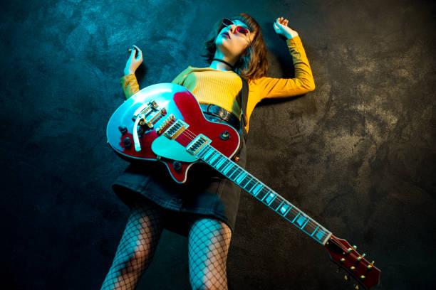 moden junge hipster-frau mit lockigen haaren mit roter gitarre in neonlicht. rockmusiker spielt elektrische gitarre. 90er-jahre-konzept. - bands der 90er stock-fotos und bilder