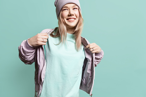 Fashion young woman in blank sweatshirt jacket takes on a blue background in pastel colors