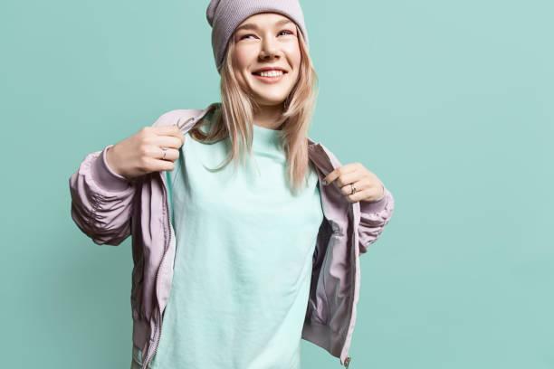 moda joven mujer en chaqueta sudadera en blanco toma sobre un fondo azul en colores pastel - moda playera fotografías e imágenes de stock