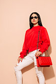 Fashion young woman in white jeans and sweater with red bag clutch in hands