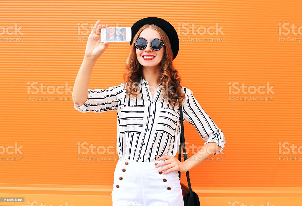 Fashion young woman model taking picture self portrait on smartphone stock photo
