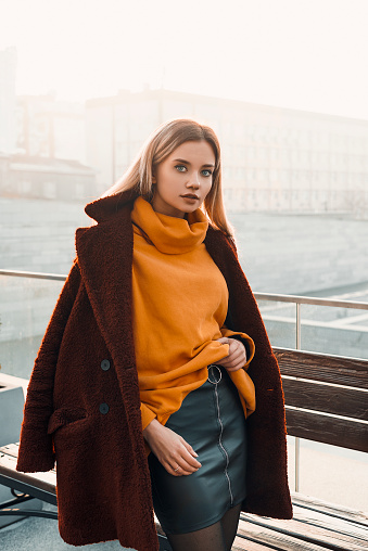 Fashion young woman posing near bench. Wearing in orange jacket and red coat and black skirt. Street urban style. Beauty blonde girl in city street