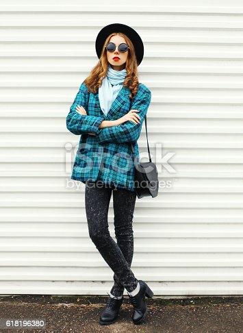 istock Fashion young woman wearing black hat checkered coat jacket handbag 618196380
