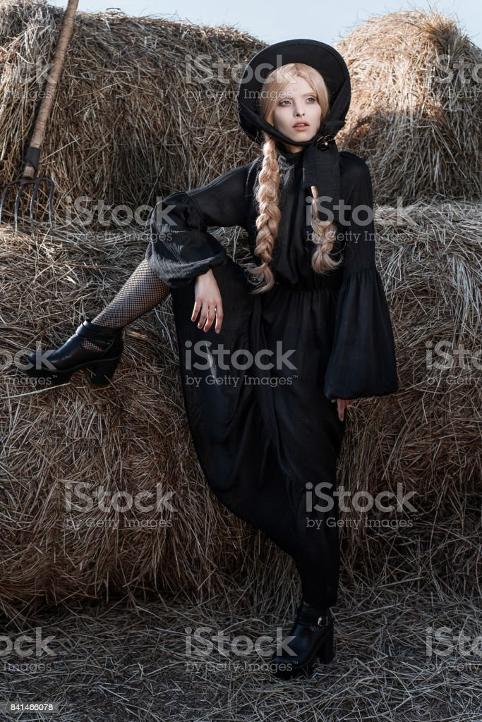 Fashion young woman wearing stylish black dress and hat at countryside. Amish fashion style. stock photo