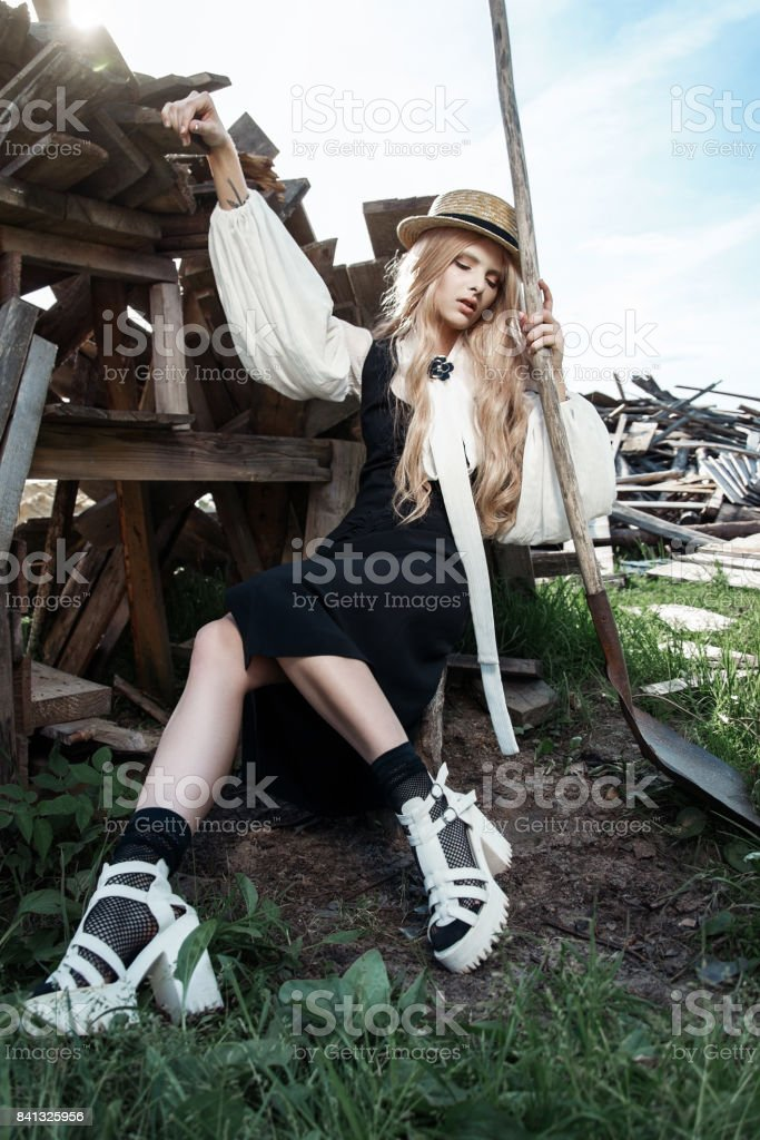 Fashion young woman wearing stylish dress and straw hat at countryside. Amish fashion style. stock photo