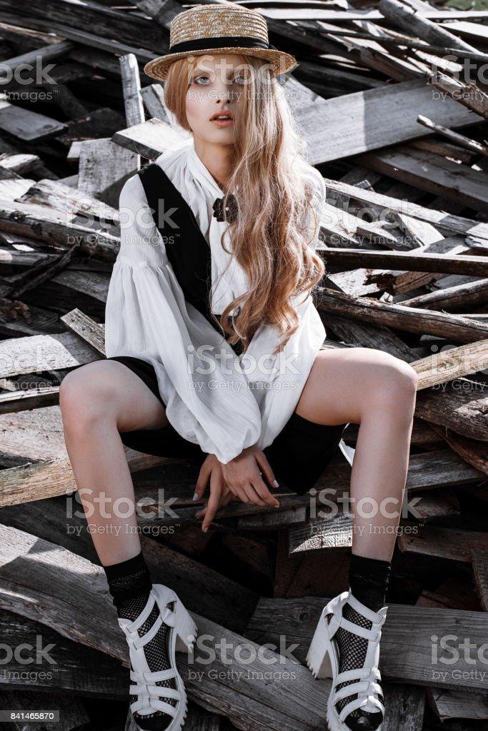 Fashion young woman wearing stylish dress and straw hat at countryside. Amish fashion style. stock photo